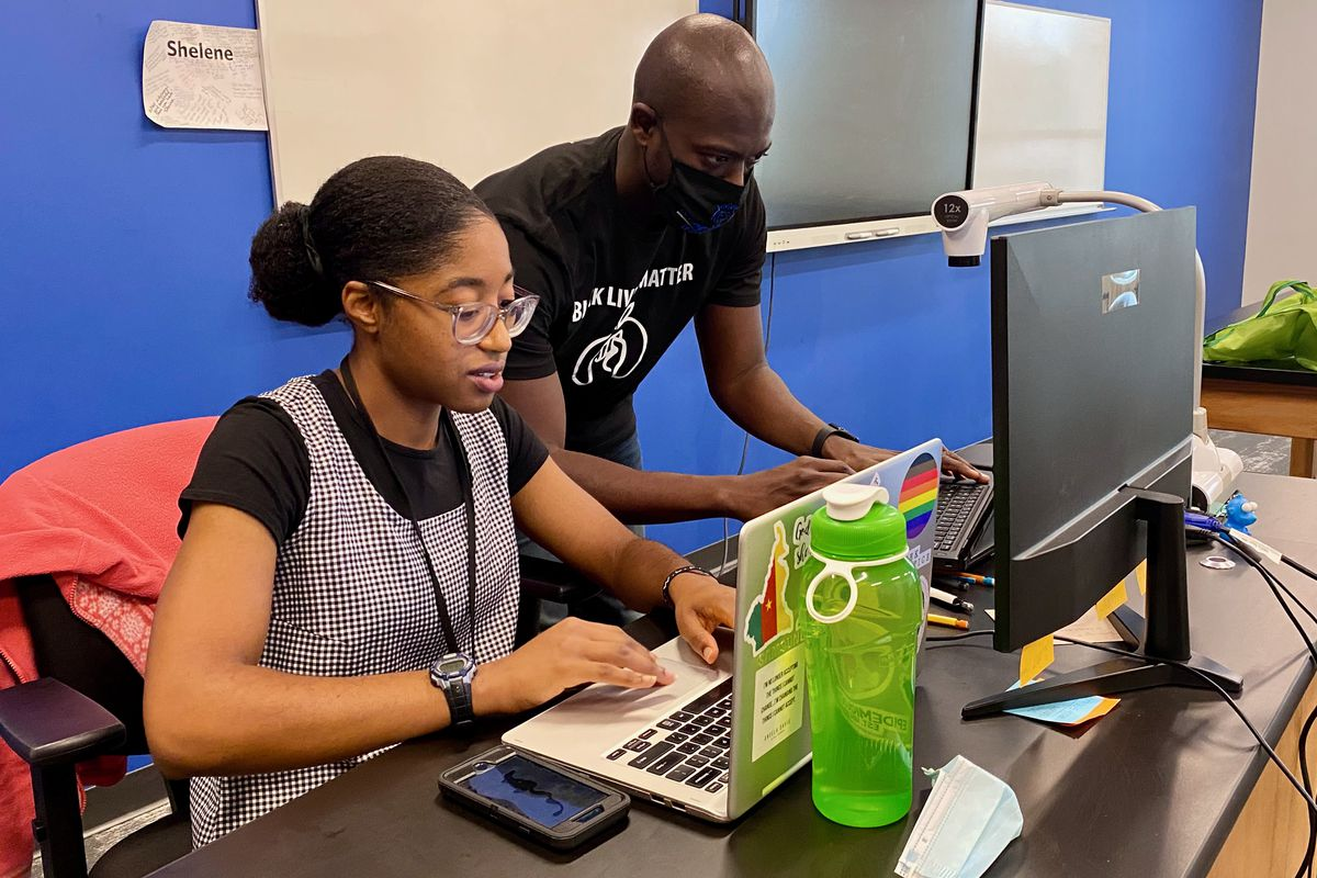 Shelene Baiyee teaches a remote lesson and David Spencer sets up at computer at KIPP Indy Legacy High School.