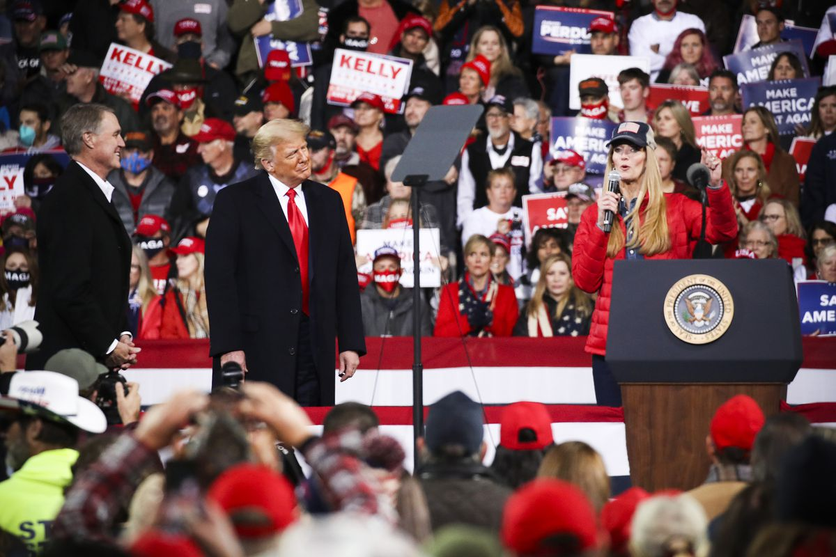 Loeffler, in a red puffer coat and dark blue denim shirt, stands behind a podium featuring the seal of the president of the US; surrounded by a crowd of Trump supporters, she speaks into a microphone. To her right, Trump and Purdue, both in dark overcoats, smile as they listen to her remarks.