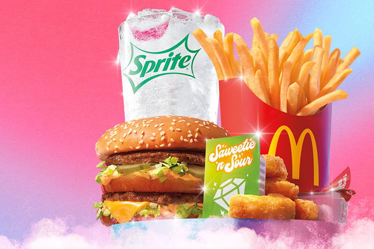 """A Sprite, big mac, fries, chicken nuggets and a packet of """"saweetie and sour sauce"""" in front of a pink and blue background"""