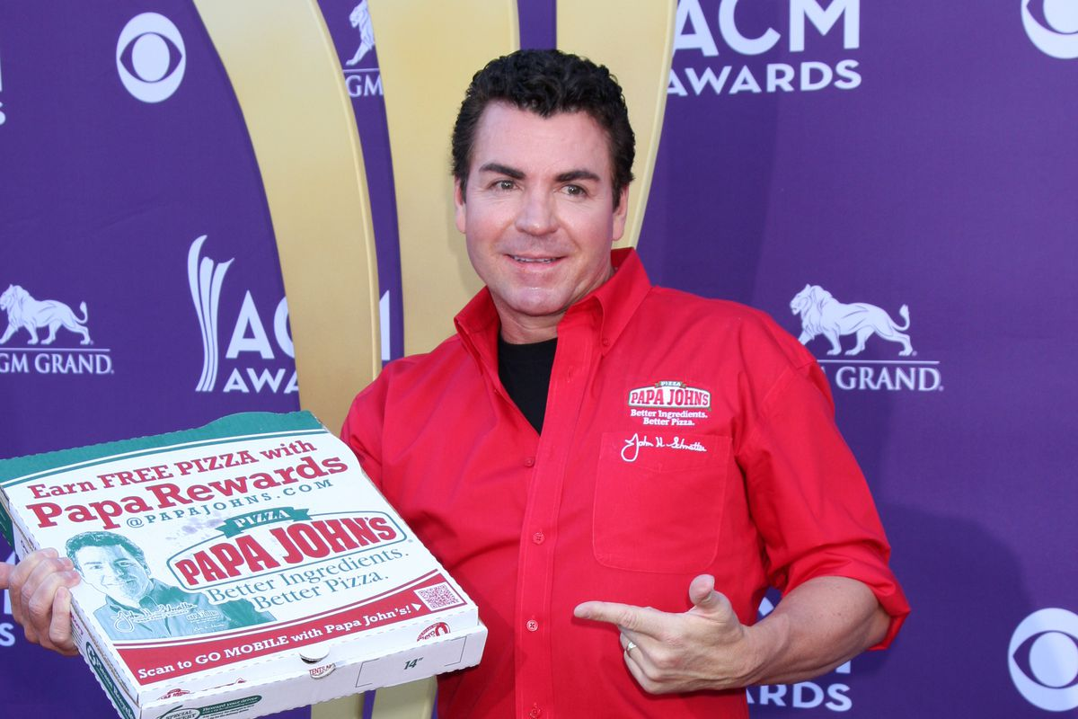 John Schnatter stands on a red carpet pointing to a Papa John's pizza box in his hand.