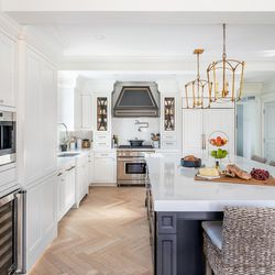 The new open-plan layout of the kitchen/dining area offers long sight lines and a feeling of spaciousness and conviviality. At rear is the pro-style range and vent hood.