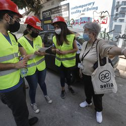 People who volunteered to help clean damaged homes and give other assistance, takes notes from a woman on a street that was damaged by last week's explosion, in Beirut, Lebanon, Tuesday, Aug. 11, 2020. In the absence of the state, acts of kindness and solidarity have been numerous and striking. Many extended a helping hand far beyond their circle of friends or family, taking to social media to spread the word that they have a room to host people free of charge.