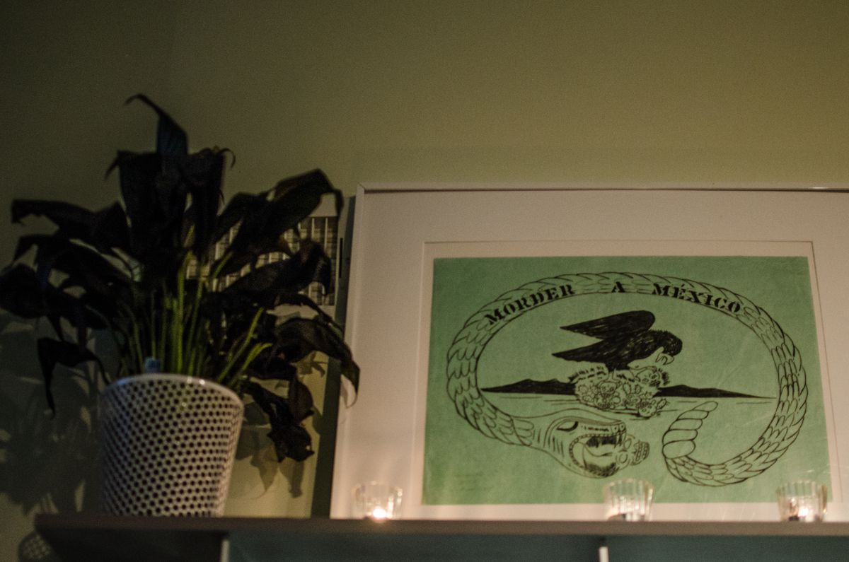 """A potted plant sits next to a framed piece of art that reads """"Morder a Mexico"""""""