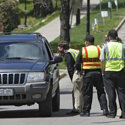 Boulder County Sheriff's deputies and University Police check occupants of a vehicle for student ID at the University of Colorado in Boulder, Colo., on Friday, April 20, 2012. The university closed the  campus to prohibit an annual 420 marijuana smoke out.