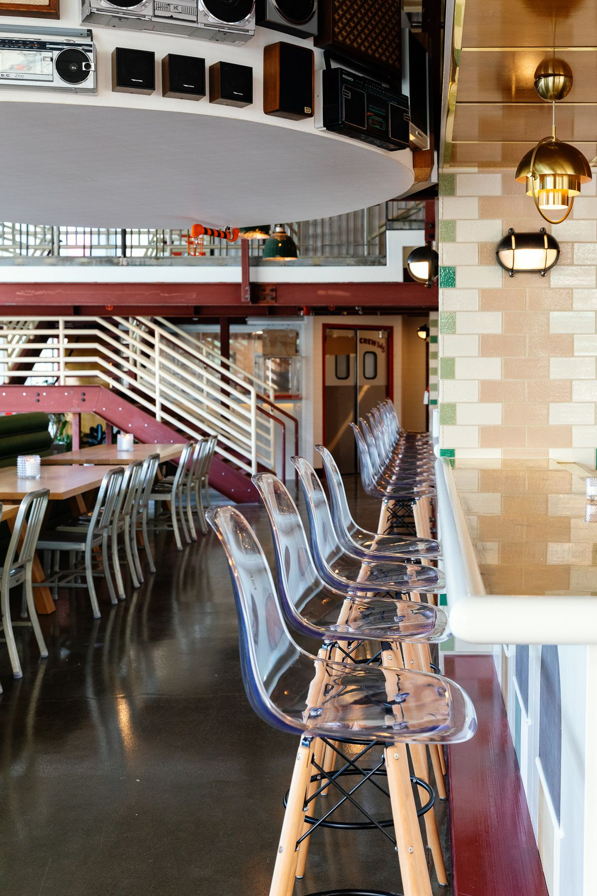 Chairs at a bar and table seating. Radio speakers hang over the dining room