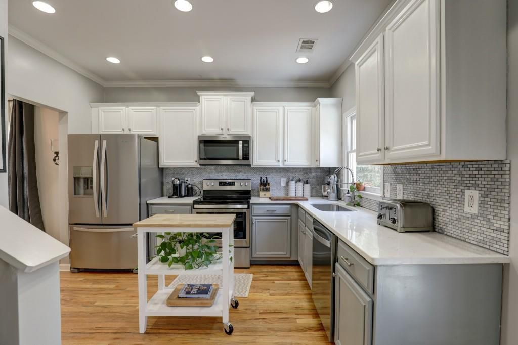 Kitchen with white cabinets and countertops, stainless appliances and an island.