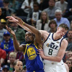 Utah Jazz forward Jonas Jerebko (8) fouls Golden State Warriors forward Kevin Durant (35) during the game at Vivint Arena in Salt Lake City on Tuesday, April 10, 2018.