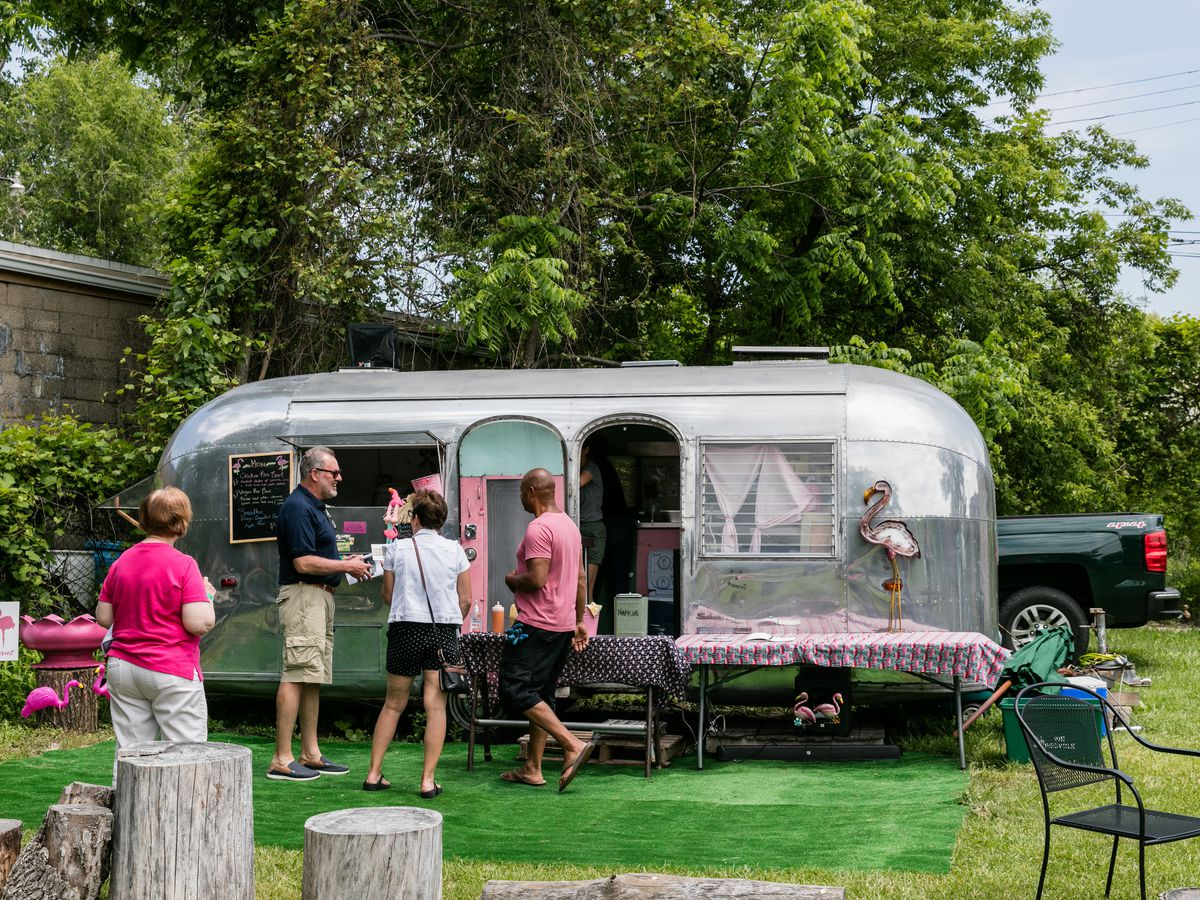 A chrome airstream trailer is parked in a grassy area on a sunny day with a fake grass rug in front. Customers in shorts gather around the trailer.