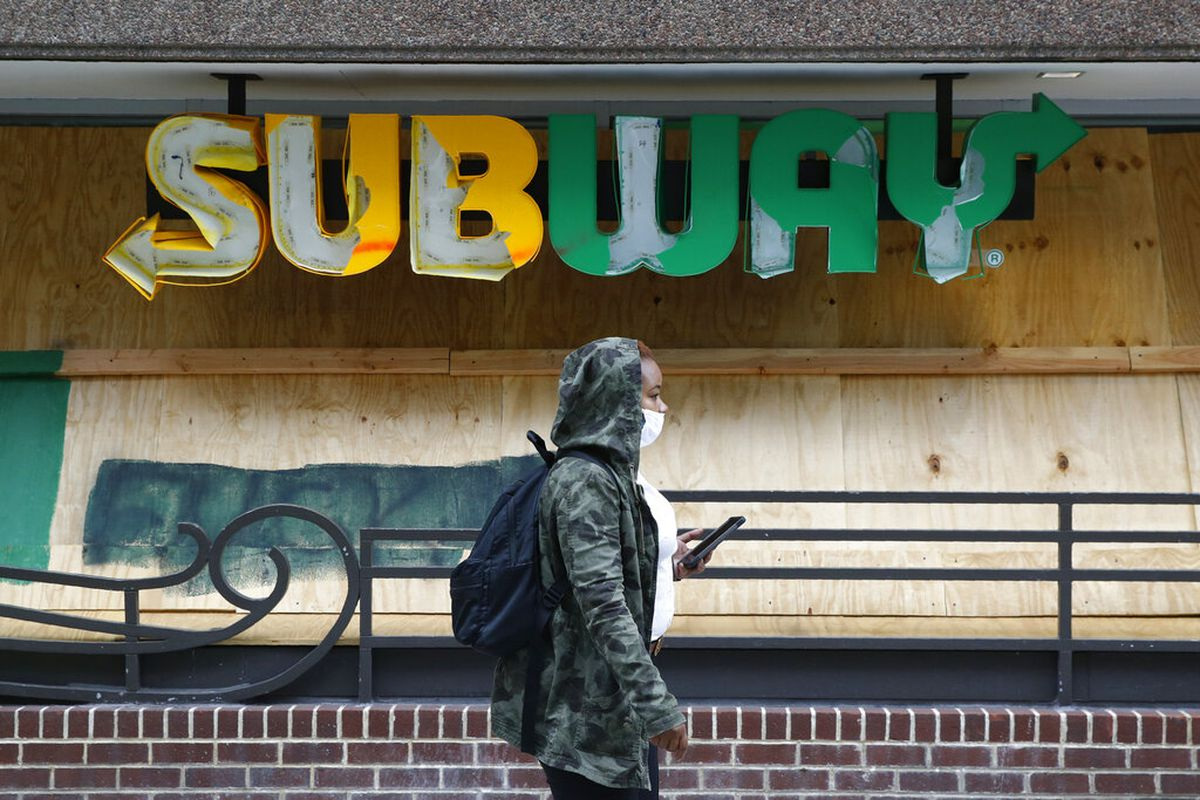 A woman wears a face mask near a Subway restaurant sign.