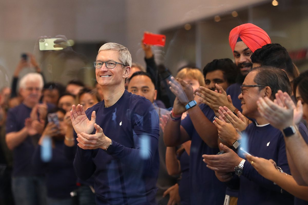 Apple CEO Tim Cook applauds along with Apple store employees
