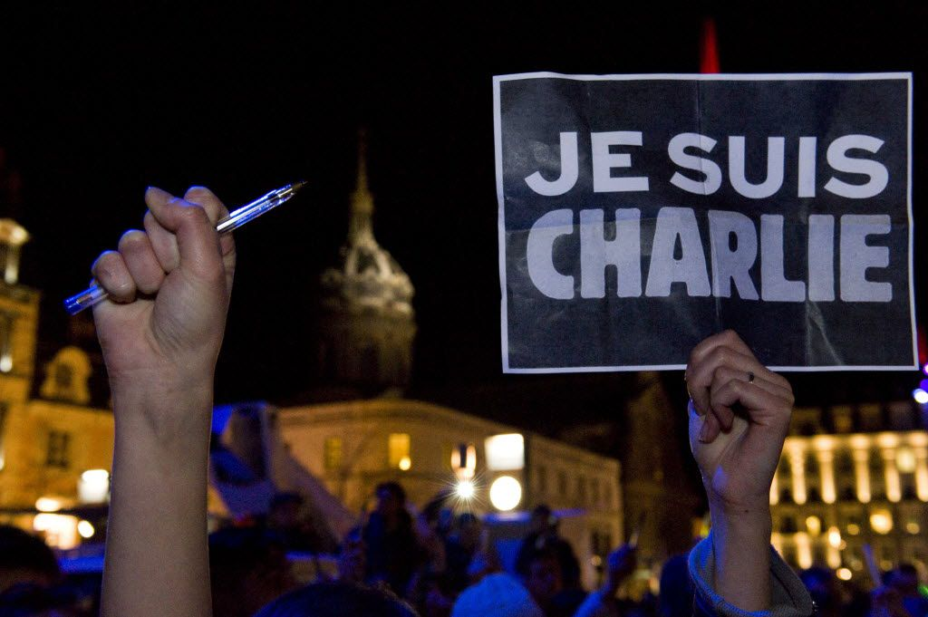 """<small><strong>A person holds a placard reading, """"I am Charlie"""" in Clermont-Ferrand. 