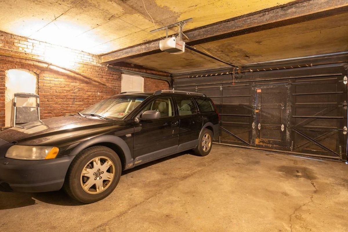 A parking spot in a garage with its door closed, and there's a long vehicle next to the spot in another space.