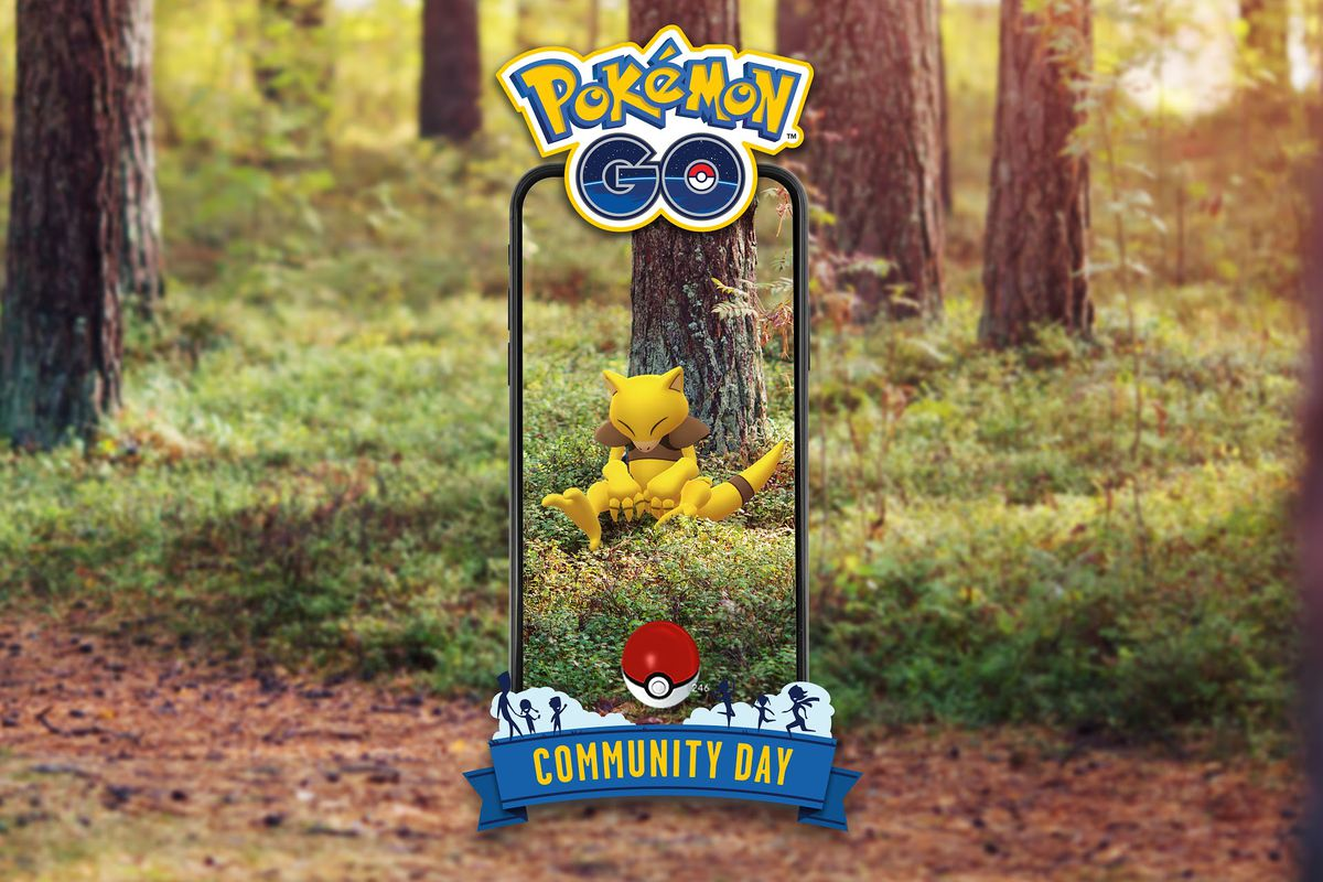 An Abra floats in the woods, only visible on somebody's phone through AR, with Pokémon Go Community Day branding
