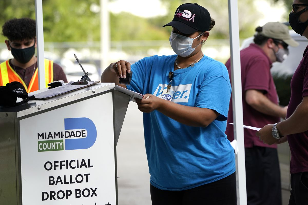 In this Monday, Oct. 26, 2020, file photo, an election worker stamps a vote-by-mail ballot dropped off by a voter before placing it in an official ballot drop box before at the Miami-Dade County Board of Elections in Doral, Fla.