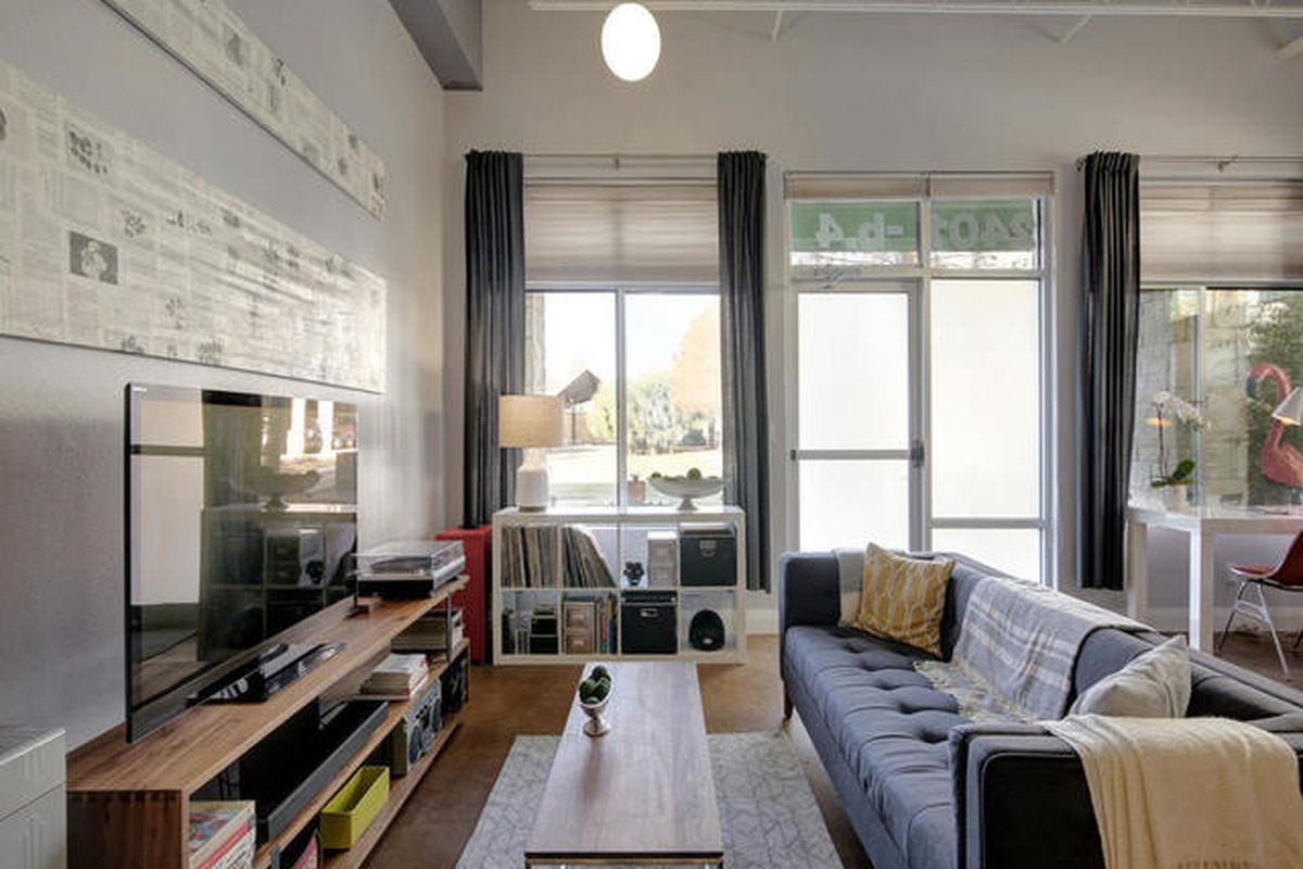 Big contemporary loft with big windows and oor on one end, concrete floors, couch, entertainment area, etc.