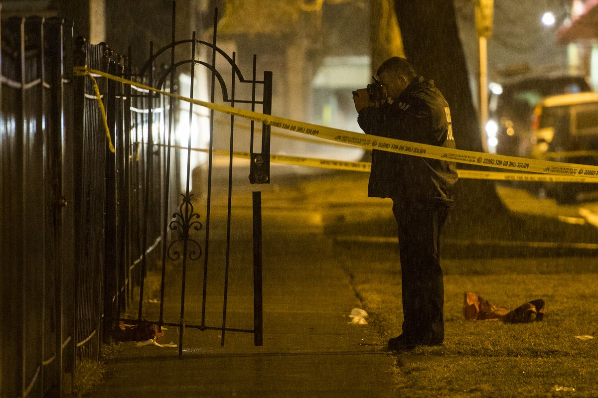 An officer takes photos Tuesday evening at the scene of a shooting that left three people wounded in the 1500 block of North Linder. | Tyler LaRiviere/Sun-Times