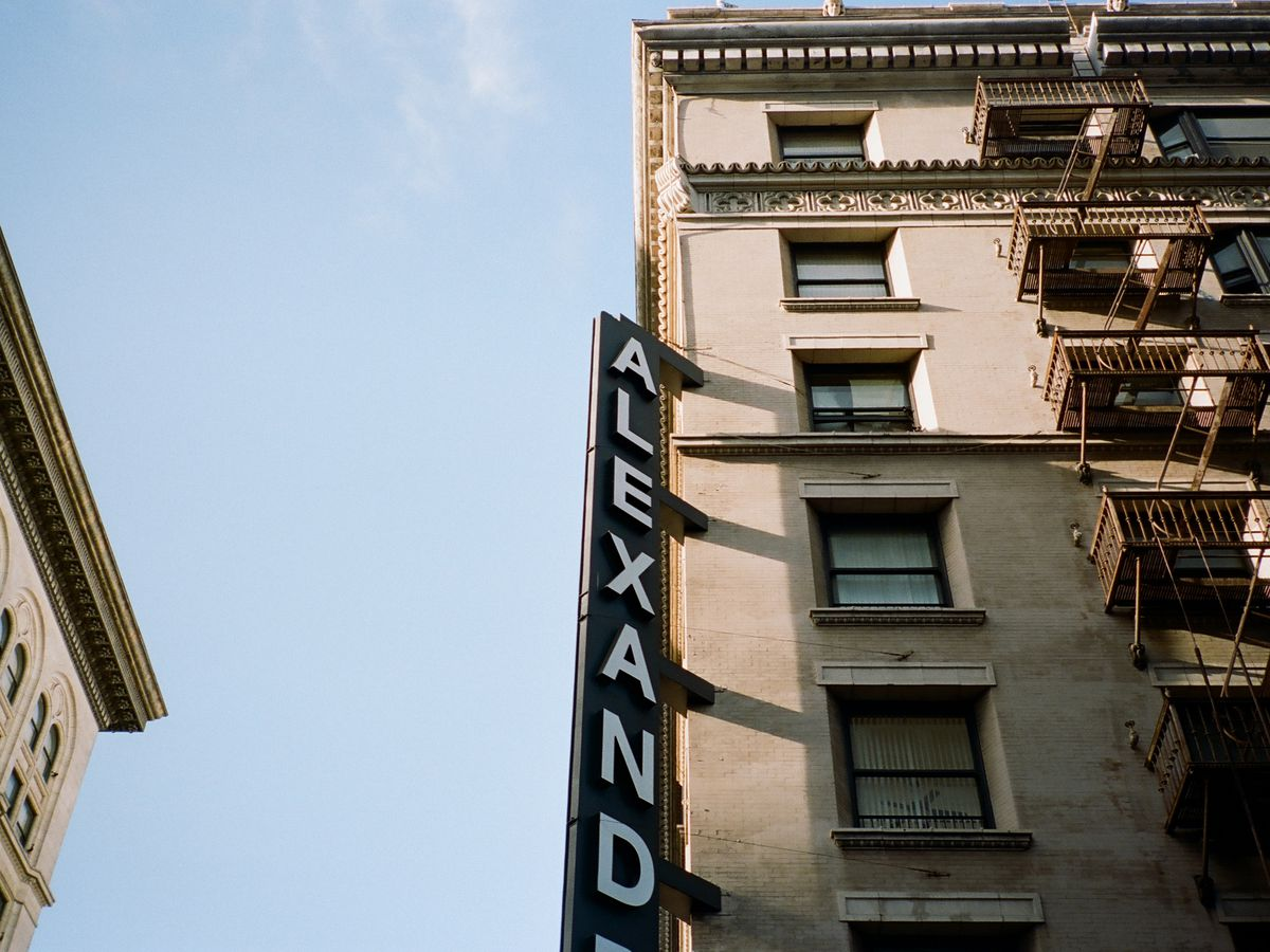 A tan building with brown fire escapes. There is a sign on the building that reads: Alexandria.