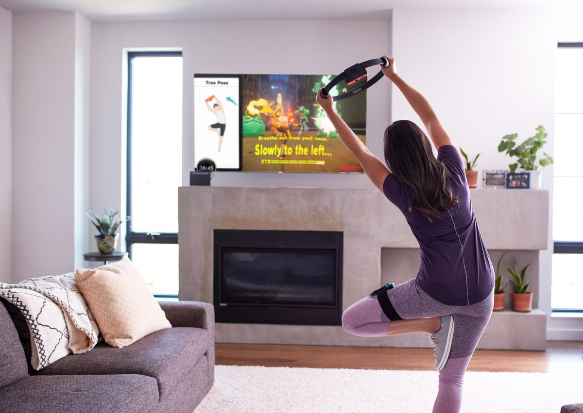 une femme en tenue d'exercice maintient une pose de yoga avec le Ring-Con tout en jouant au Ring Fit Adventure de Nintendo