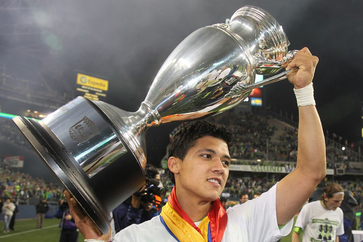 Wrapped in the colors of Colombia Montero hoists an Open Cup trophy