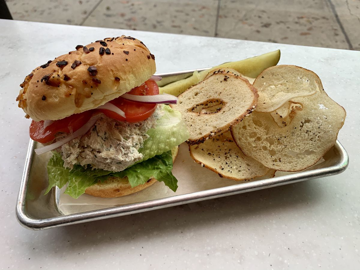 A vegan smoked whitefish salad on an onion roll beside a pickle and pile of bagel chips.
