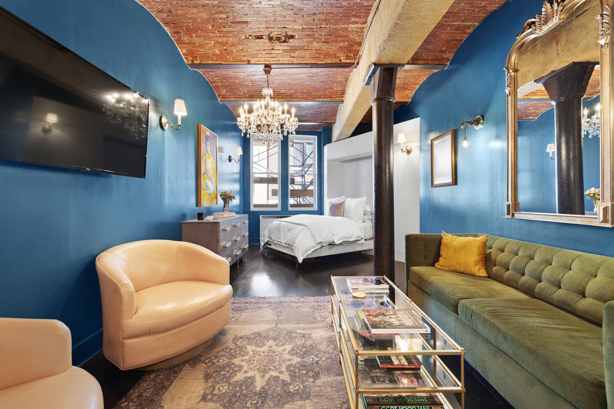 A living area with bright blue walls, vaulted ceilings, exposed brick, a green couch, and a glass coffee table.