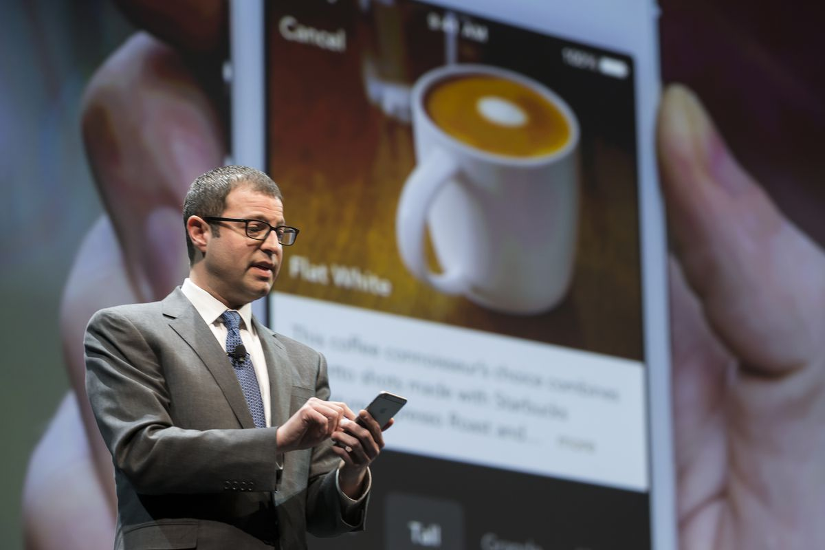 Starbucks executive Adam Brotman onstage looking at a mobile phone in front of a screen showing a cup of coffee on the Starbucks mobile app.