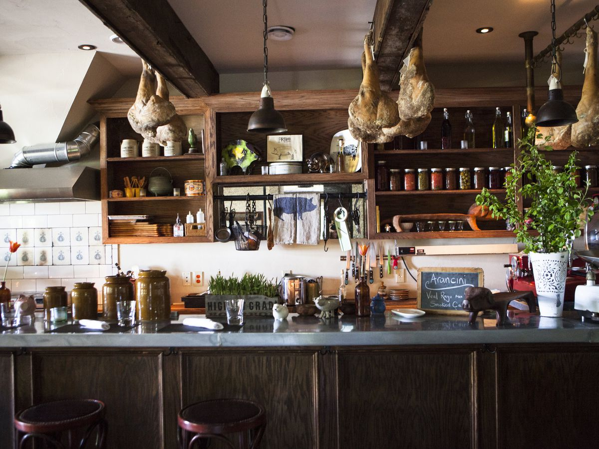A kitchen counter with open shelving packed with dishes and pickle jars, a counter topped with jars and bunches of herbs and a chalkboard sign, decorative backsplash, and dried meat hanging beside pendant lights near the ceiling
