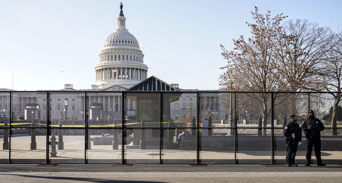 Capitol police officers stand outside of fencing that was installed around the exterior of the Capitol grounds on Thursday.