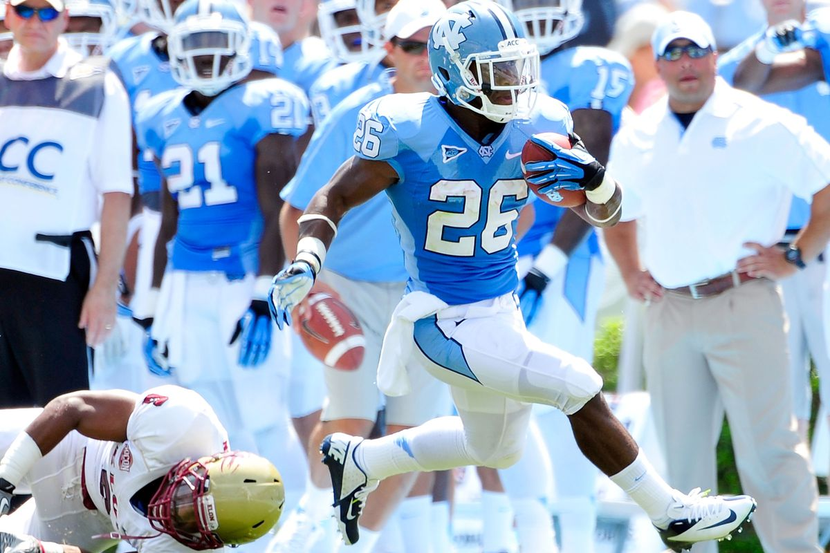 Giovani Bernard #26 of the North Carolina Tar Heels breaks away from Miles Williams #2 of the Elon Phoenix to score a touchdown. Bernard later left the game with an injured knee.