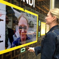 A woman virtually tries on Fendi sunglasses at Bloomingdale's.