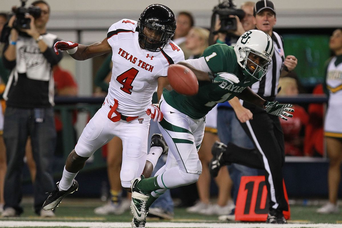 ARLINGTON, TX - NOVEMBER 26:  Kendall Wright #1 of the Baylor Bears drops a pass against Derrick Mays #4 of the Texas Tech Red Raiders at Cowboys Stadium on November 26, 2011 in Arlington, Texas.  (Photo by Ronald Martinez/Getty Images)