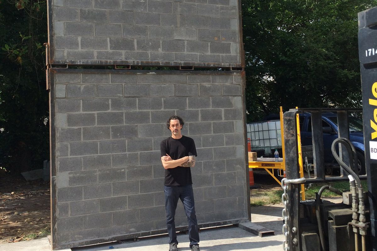 A photo of the artist Joseph Guay constructing his thought-providing barrier.