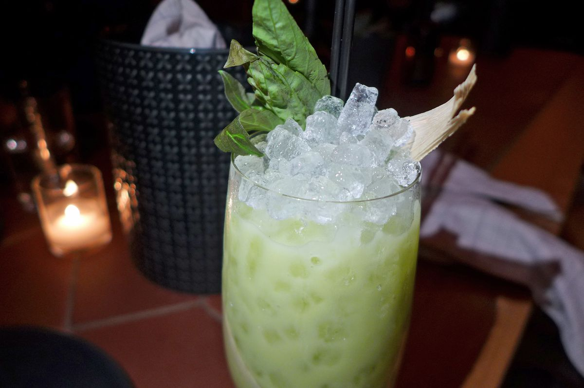 A greenish drink with crushed ice in a tall glass.