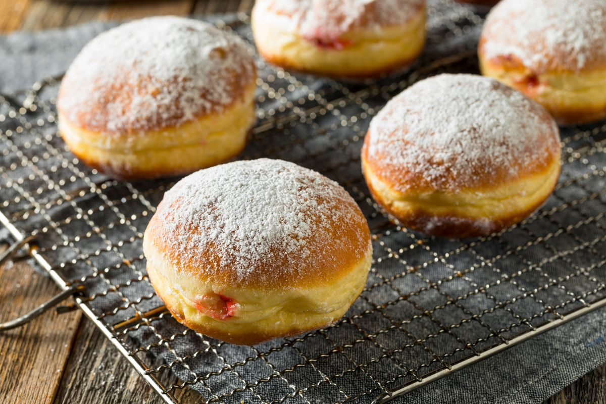 Polish paczki donuts with jelly filling on a drying rack.