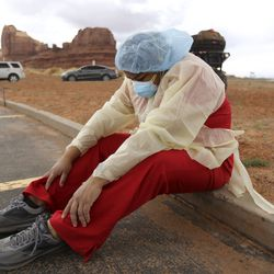 """""""My feet hurt,"""" says Denise Begaye, an X-ray technician with the Monument Valley Health Center, as she sits on a curb and takes a break from COVID-19 testing outside of the center in Oljato-Monument Valley, San Juan County on Thursday, April 16, 2020. The mobile testing team tested 581 people on Thursday."""