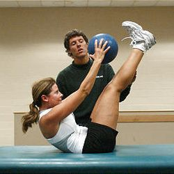 Kim Faulkner of Murray performs medicine ball crunches with personal trainer Scott Browning at the Sports Mall. Crunches strengthen an athlete's core stability and abdominal muscles. A personal trainer is a great addition to any get-fit routine.