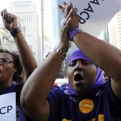 Jacqueline Coles, left, and Karmella Sams cheer during the NAACP voter ID rally to demonstrate the opposition of Pennsylvania's new voter identification law, Thursday, Sept. 13, 2012, in Philadelphia. Pennsylvania's Supreme Court justices are scheduled to hear arguments over whether a new law requiring each voter to show valid photo identification poses an unnecessary threat to the right to vote.