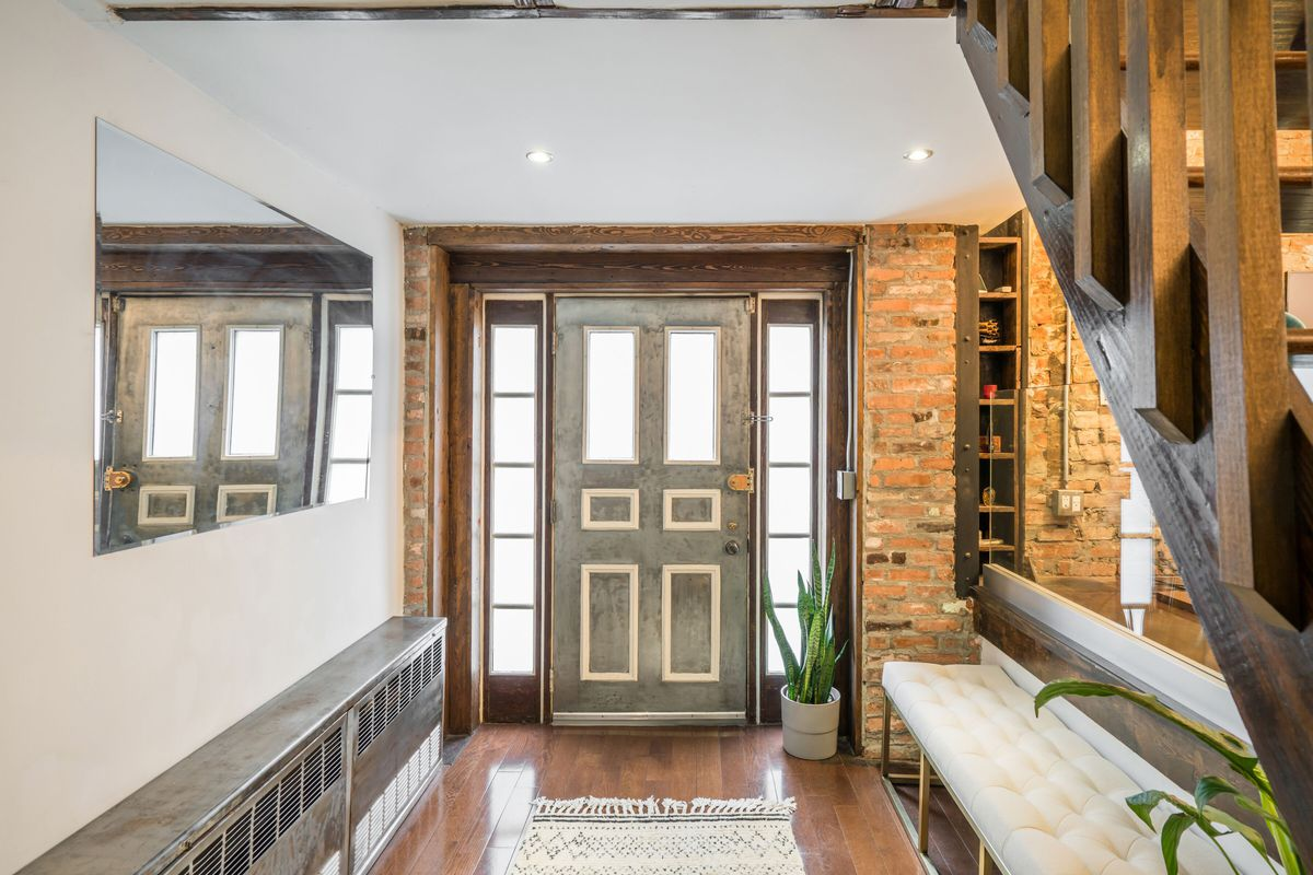 An entrance with exposed brick, hardwood floors, and a wooden staircase on the right side.