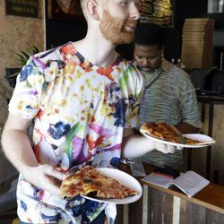 In this Wednesday, Sept. 12, 2012 photo, Brian Dwyer serves up a costumer's order at Pizza Brain in Philadelphia. Hundreds of people turned out for the grand opening of Pizza Brain this month in Philadelphia's Fishtown neighborhood. It's a restaurant where visitors can eat a slice or two of artisan pie while gawking at a pizza-related photos, records, knickknacks and videos.