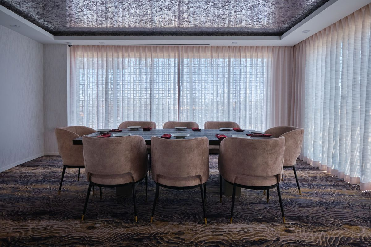 A long table with taupe chairs and white sheer curtains behind it