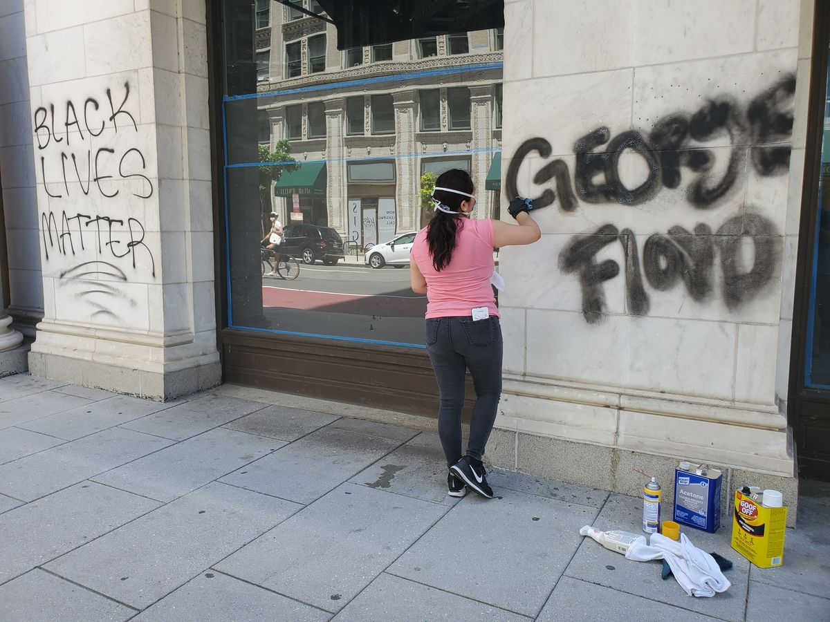A woman attempts to remove graffiti from the outside of the former Woodward Table space Sunday in downtown D.C.
