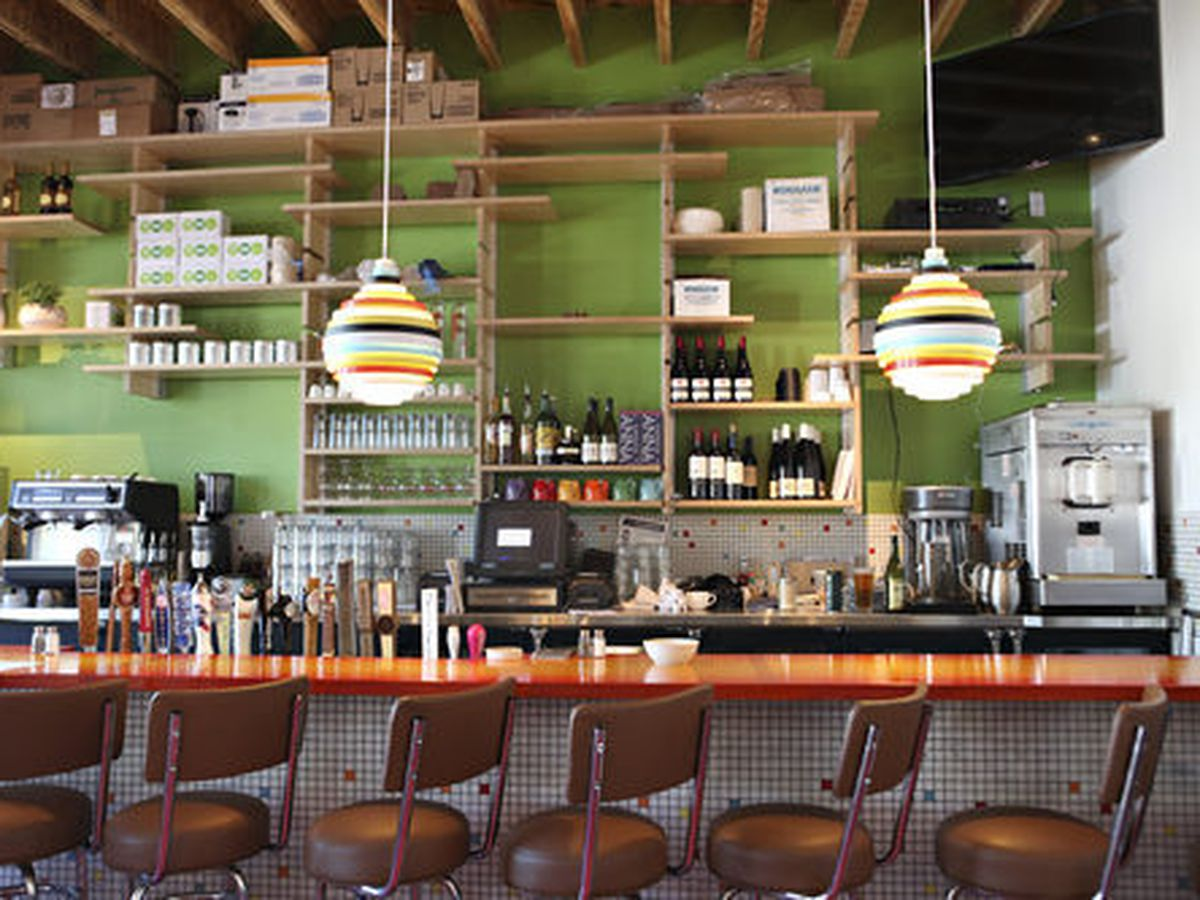 A bar with a lime green background and a lineup of brown stools