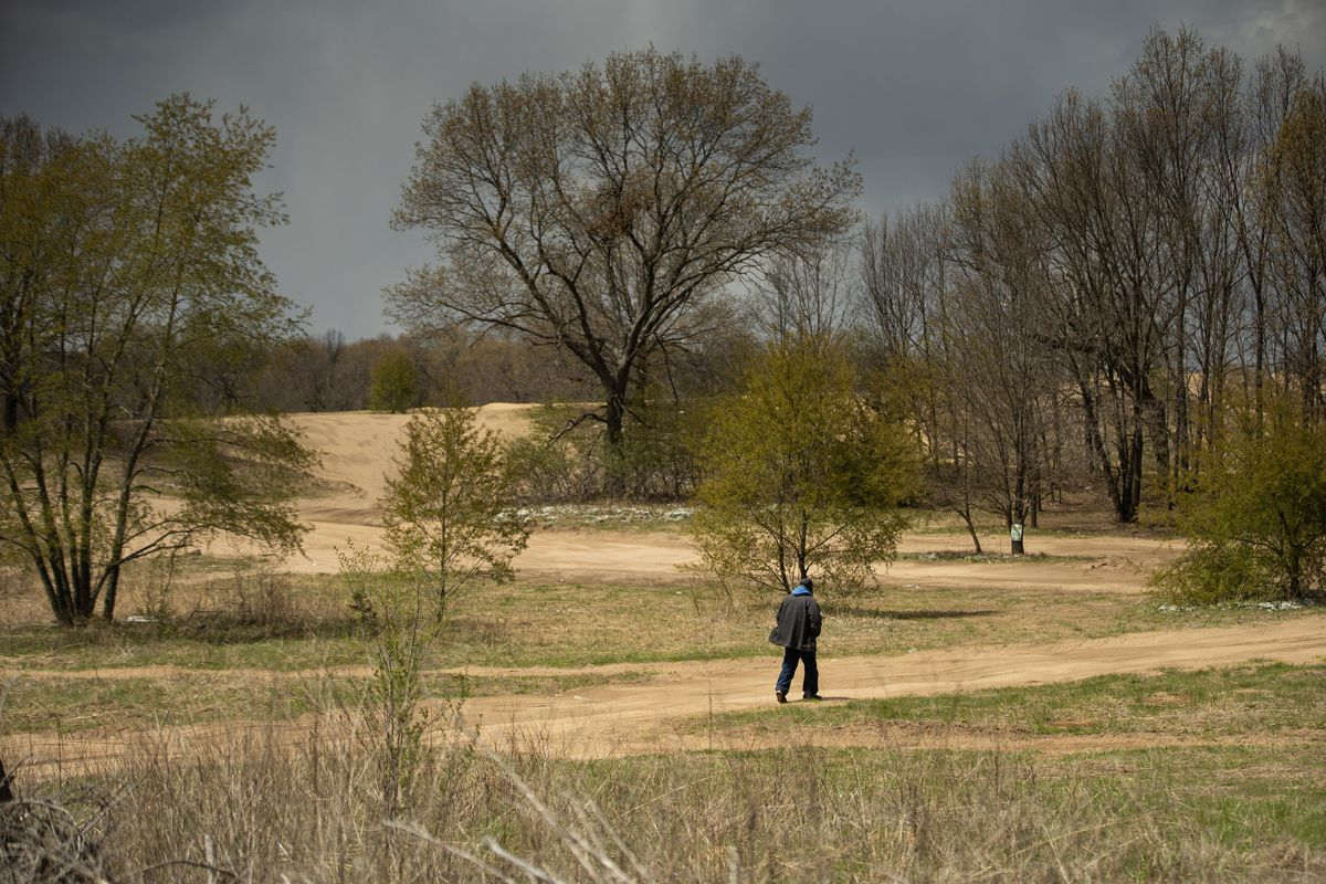 A man walks toward sand dunes in Pembroke Township, home to a rare ecosystem that's attracted the interest of conservation groups.