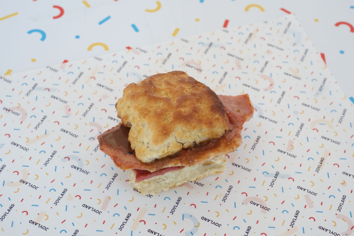 joyland printed paper with a ham stacked biscuit sandwich