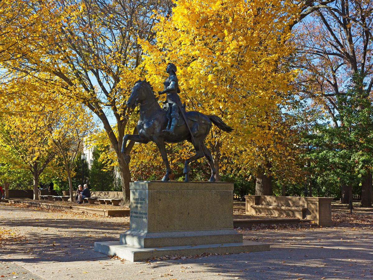 A statue of a woman riding on a horse and holding a sword in the middle of a park with trees in yellow and green.