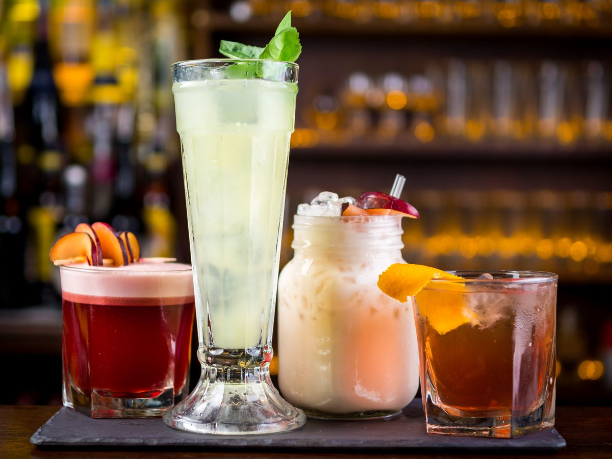 Four drinks in varied size glasses on a bar countertop