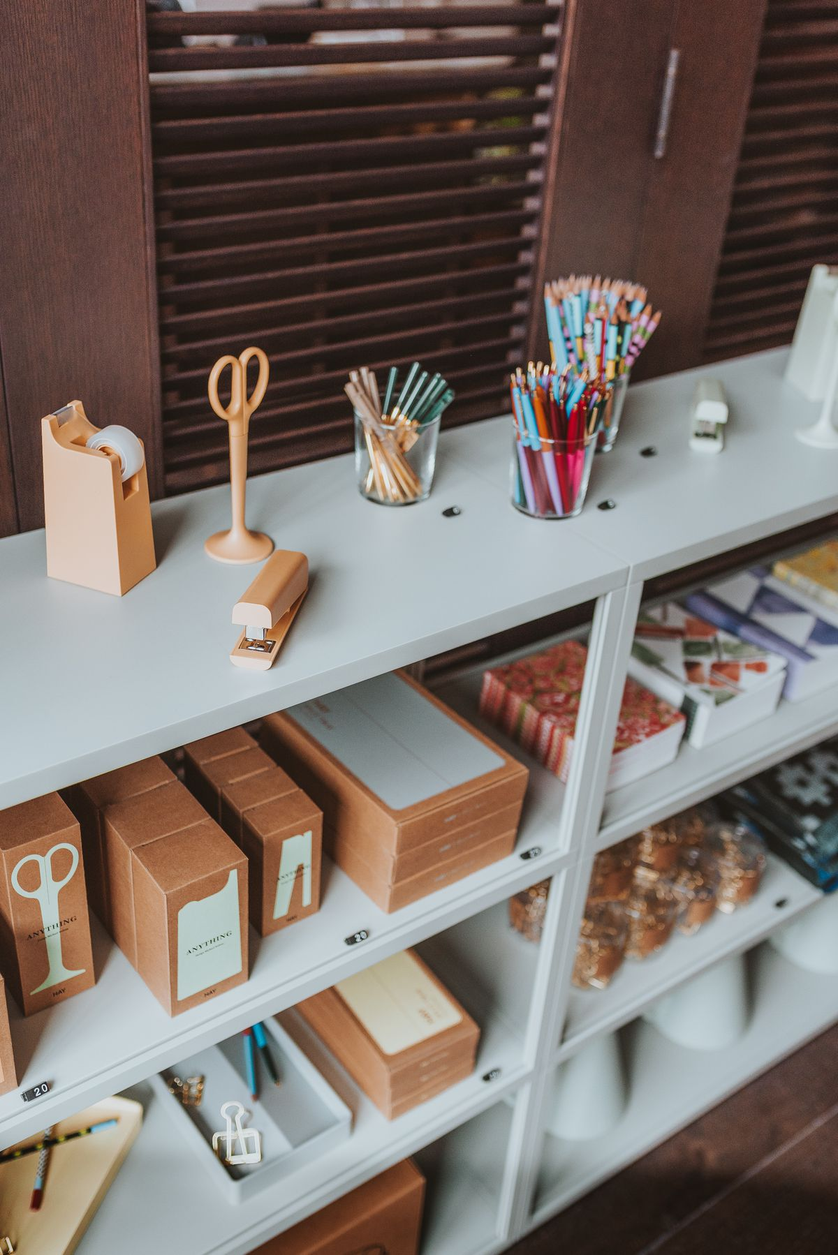 A close-up of the shelve with desk items like a matching tape dispenser, stapler, and scissors. There are three glass cups with colorful pencils.