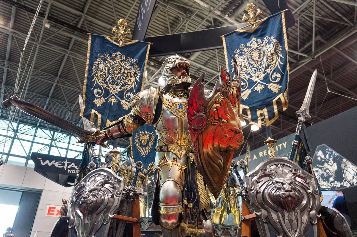 a close-up of a life-size model of an Alliance soldier from the movie Warcraft, with Alliance banners and shields around him, at the Weta Workshop booth at NYCC 2015