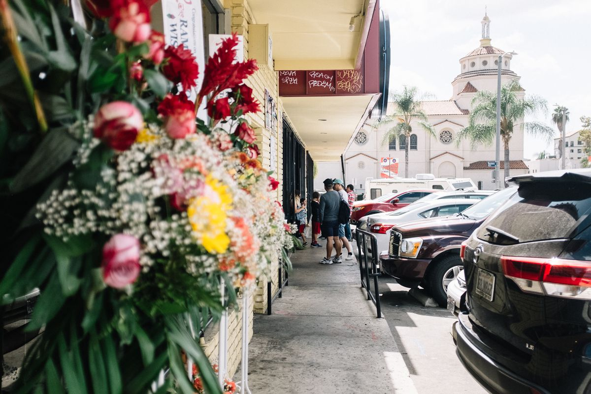 Close-up of a business in a strip mall. Customers lined up outside. Flowers—roses, baby's breath—spill out of a window box in the forefront. A church is in the background.
