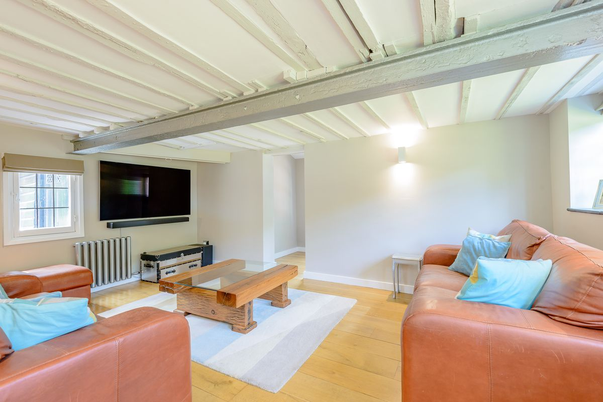 TV room with wood beam ceiling